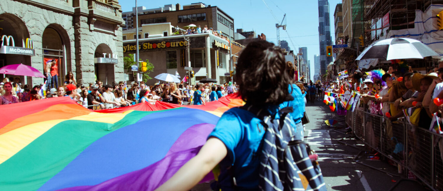 A volunteer holding part of the Pride Flag during the parade