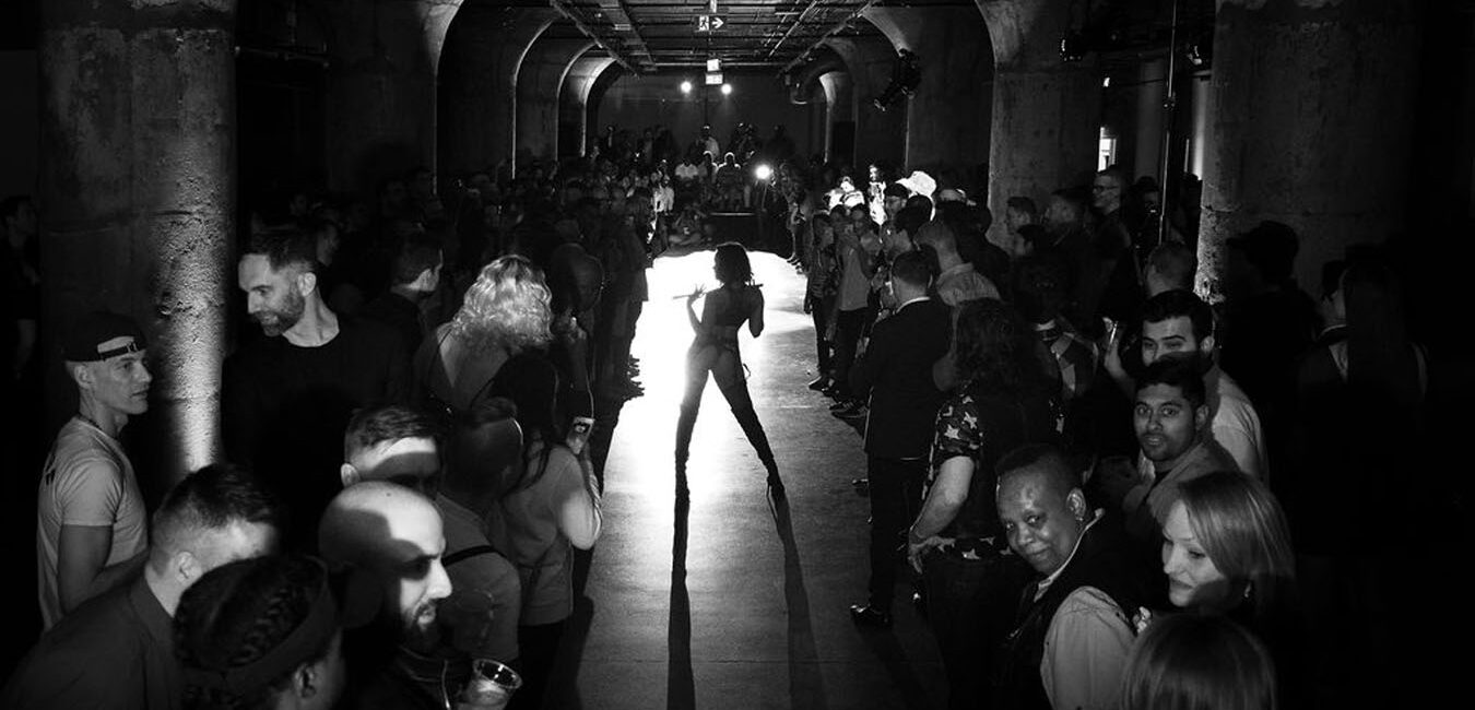 A person poses in the middle of a model runway
