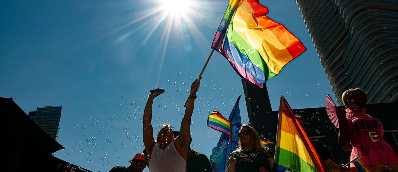 A person waving a LGBTQ flag on a float
