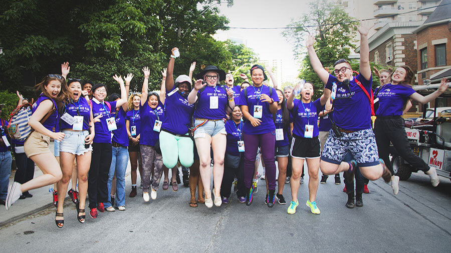 A group of volunteers jumping together in the middle of the street.