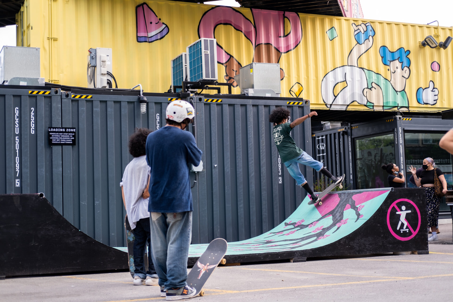 two skateboarders are looking at skateboarder on the ramp