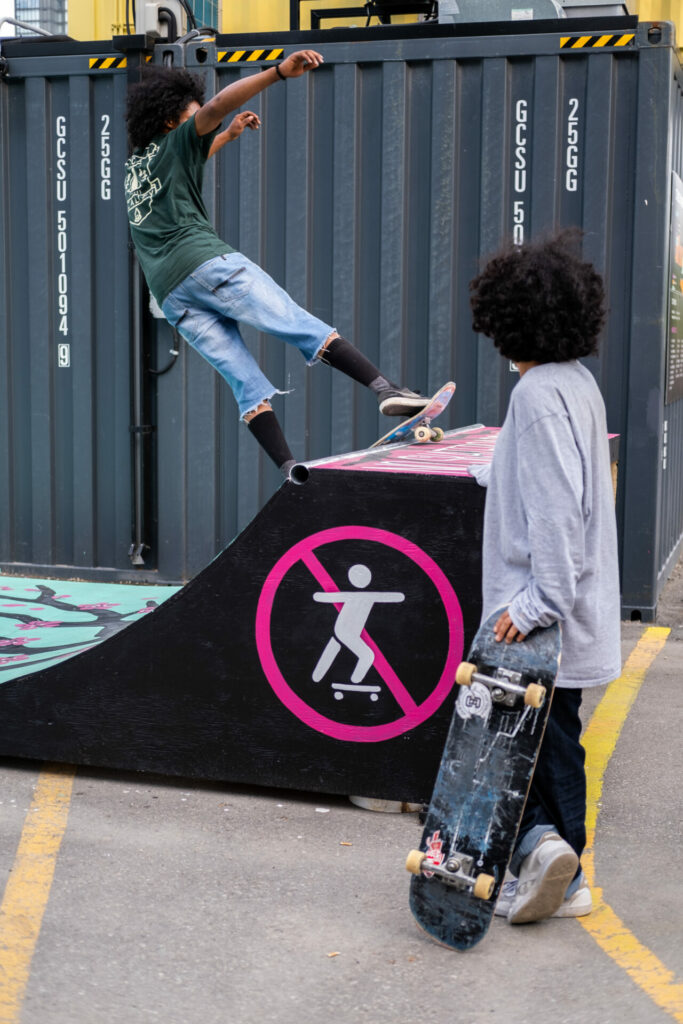 a skaterboarder on the ramp while another skaterboarder looks on