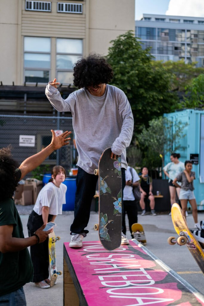 a crowd cheering on a skateboarding who is standing on top of the ramp