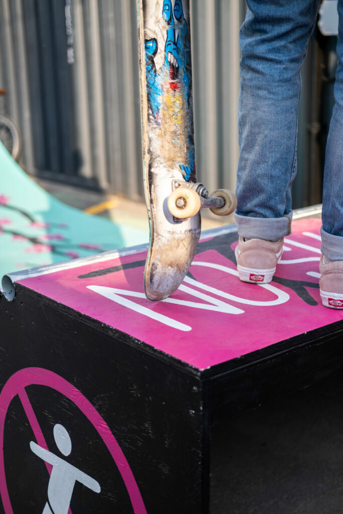 the legs of a skateboarder and their board on the top of the ramp