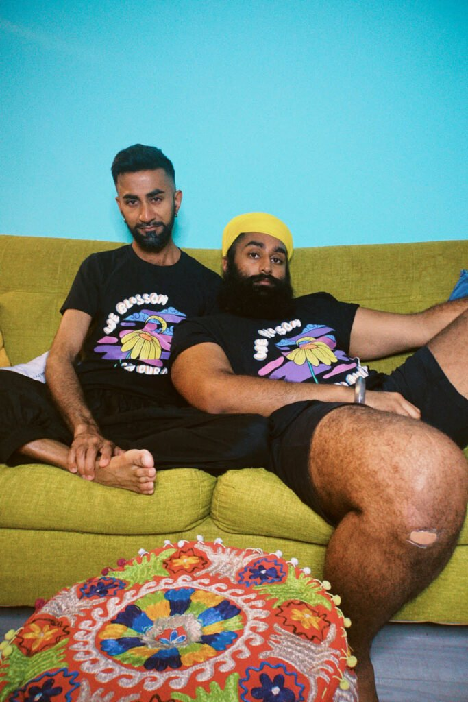 Two people with Frizz Kid's shirts on a couch