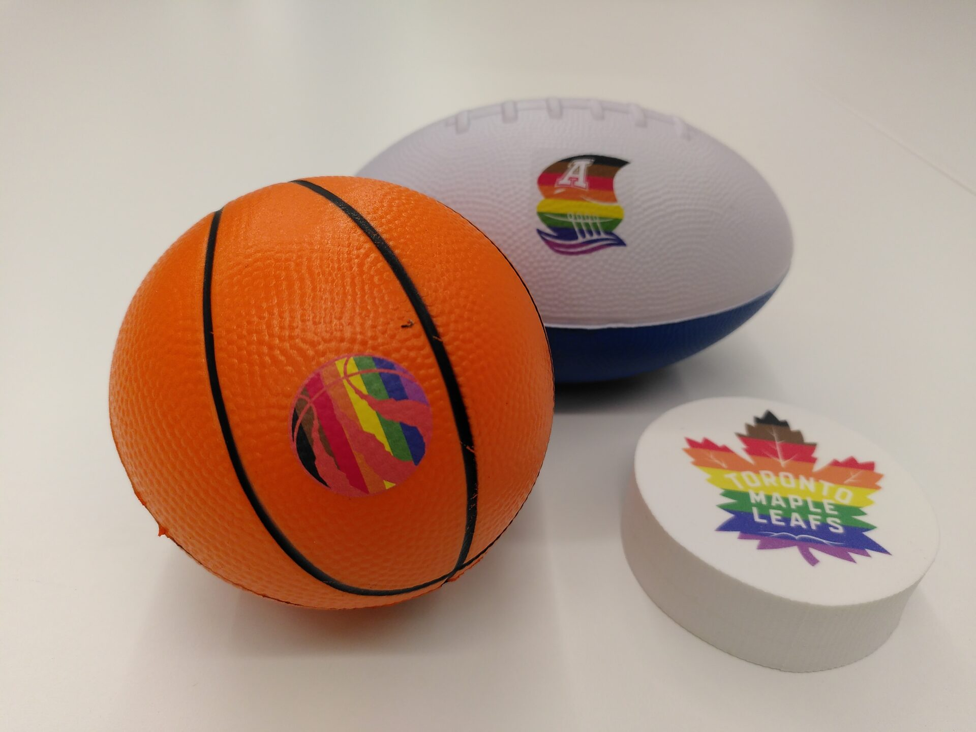 A MLSE Themed tiny basketball, football and puck